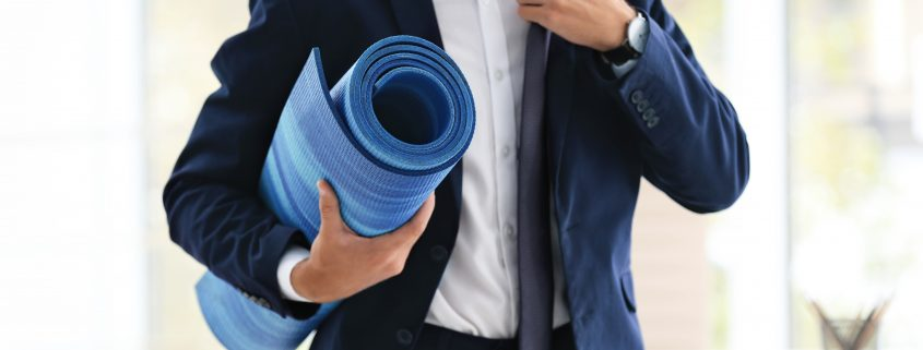 Young businessman holding yoga mat in office.